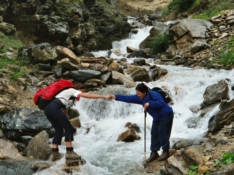 Deux trekkeurs traversant une rivière